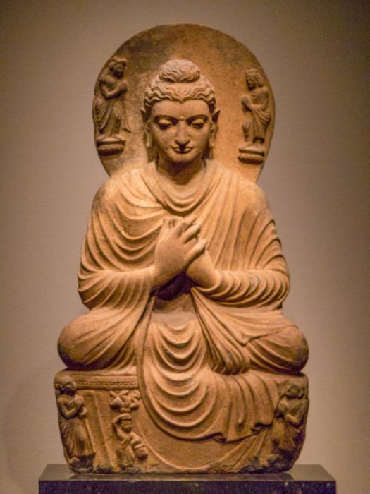 にょらいざぞう片岩 パキスタン・ガンダーラ 高77.3 クシャーン朝 2-3世紀  通肩に衣をつけ,転法輪印を結んで結跏趺坐する。波形の頭髪や,衣のひだなどの表現は,ヘレニズムの影響を色濃く残し,東西文化の交流によって生まれたガンダーラ美術の性格をよく物語る。頭光には,仏陀の左に,円筒形の宝冠を戴いたインドラ(帝釈天),右にブラフマー(梵天)が,それぞれ蓮台の上に立ち,仏陀を礼拝する。 国立博物館東洋館 http://www.tnm.jp/modules/r_collection/index.php?controller=dtl_img&size=L&colid=TC80&t=