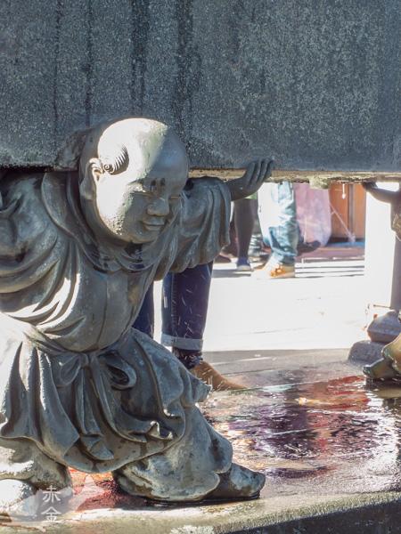 手水鉢を支える中国風の童子。鬼が支えているのは結構目にしますが、これはめずらしい